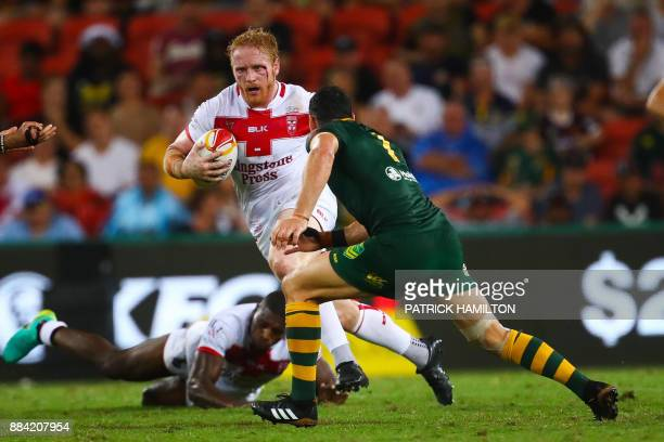 James Graham of England charges at the defence of Billy Slater of Australia during the rugby league World Cup men's final match between Australia and...