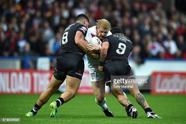 James Graham of England is tackled by Jesse Bromwich and Issac Luke of New Zealand Kiwis during the Four Nations match between the England and New...