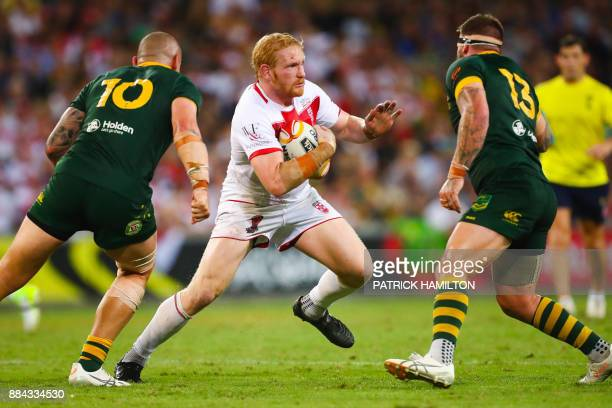 James Graham of England runs tries to avoid David Klemmer and Josh McGuire of Australia during the rugby league World Cup men's final match between...