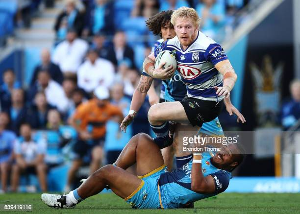 James Graham of the Bulldogs is tackled by Agnatius Paasi of the Titans during the round 25 NRL match between the Gold Coast Titans and the...