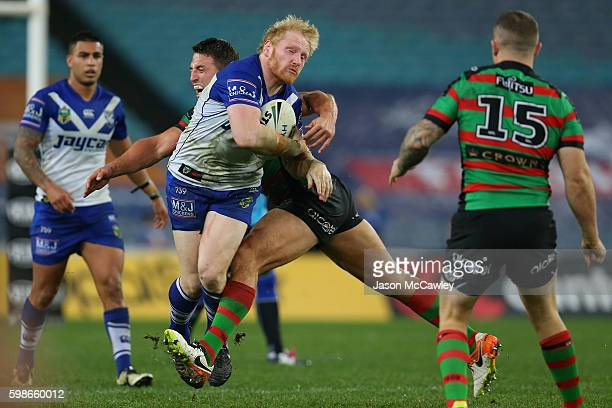 James Graham of the Bulldogs is tackled during the round 26 NRL match between the Canterbury Bulldogs and the South Sydney Rabbitohs at ANZ Stadium...