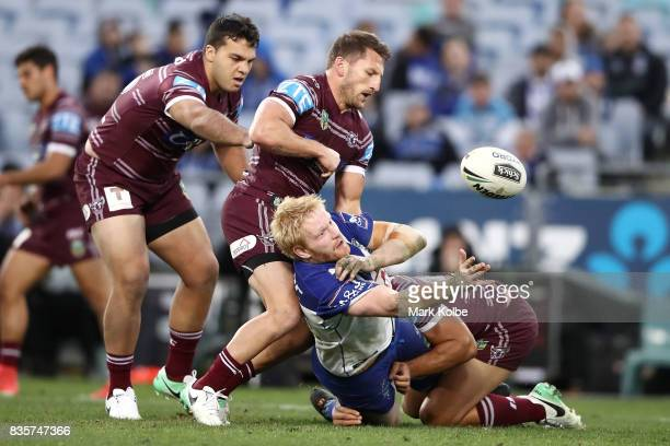James Graham of the Bulldogs passes as he is tackled during the round 24 NRL match between the Canterbury Bulldogs and the Manly Sea Eagles at ANZ...
