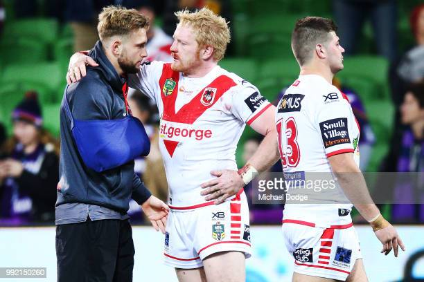 James Graham of the Dragons consoles an injured Jacob Host of the Dragons after their defeat during the round 17 NRL match between the Melbourne...