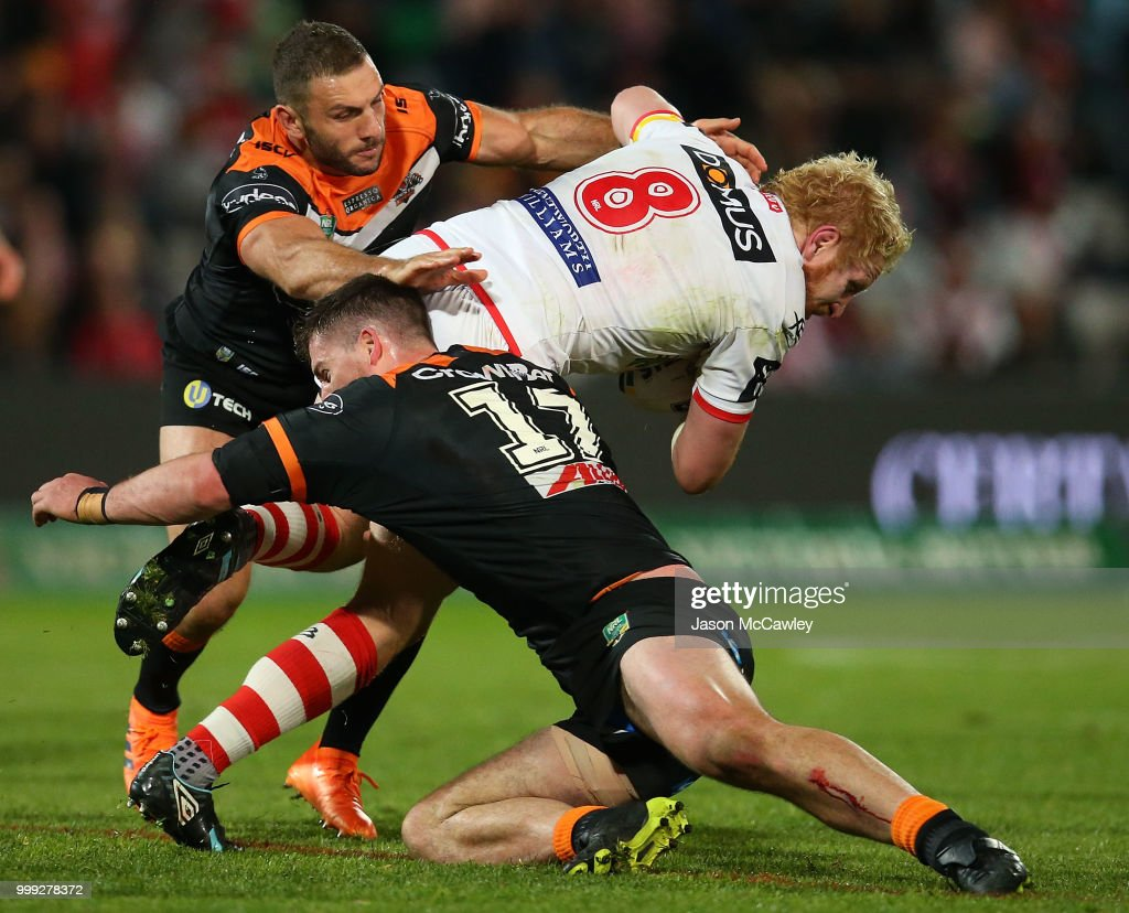 James Graham of the Dragons is tackled by Robbie Farah and Matt Eisenhuth of the Tigers during the round 18 NRL match between the St George Illawarra Dragons and the Wests Tigers at UOW Jubilee Oval on July 15, 2018 in Sydney, Australia.