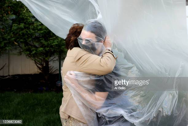 James Grant hugs his grandmother Mary Grace Sileo through a plastic drop cloth hung up on a homemade clothes line during Memorial Day Weekend on May...