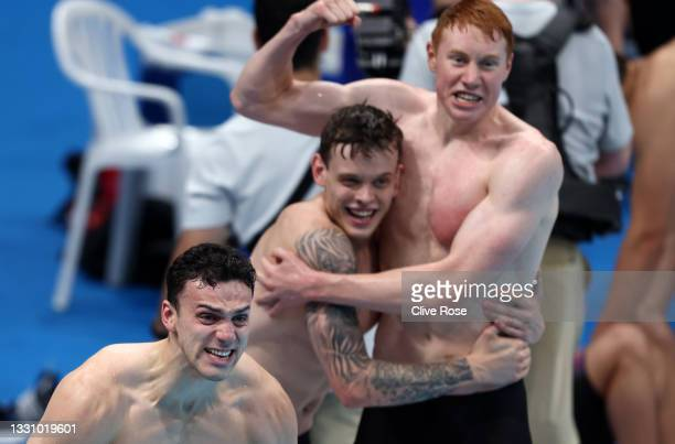 James Guy, Matthew Richards and Tom Dean of Team Great Britain react as teammate Duncan Scott swims the anchor leg during the Men's 4 x 200m...