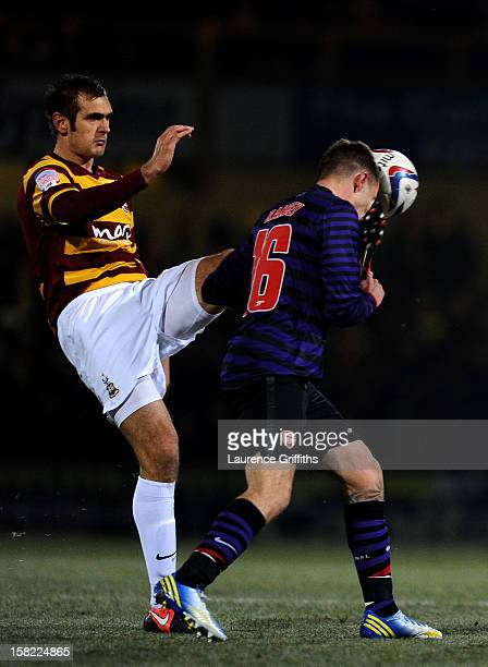James Hanson of Bradford makes contact with the face of Aaron Ramsey of Arsenal as he attempts to clear the ball during the Capital One Cup quarter...