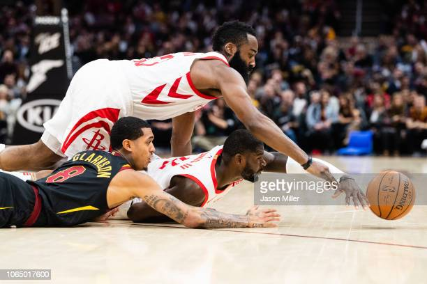 James Harden and James Ennis III of the Houston Rockets fight Jordan Clarkson of the Cleveland Cavaliers for a loose ball during the second half at...
