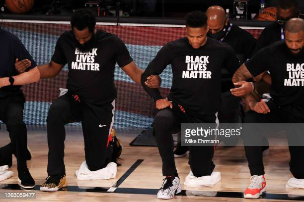 James Harden and Russell Westbrook of the Houston Rockets kneel with teammates and coaches during the national anthem before the game against the...