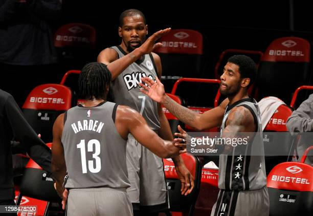 James Harden, Kevin Durant, and Kyrie Irving of the Brooklyn Nets high-five after coming off the court during the second half against the Miami Heat...
