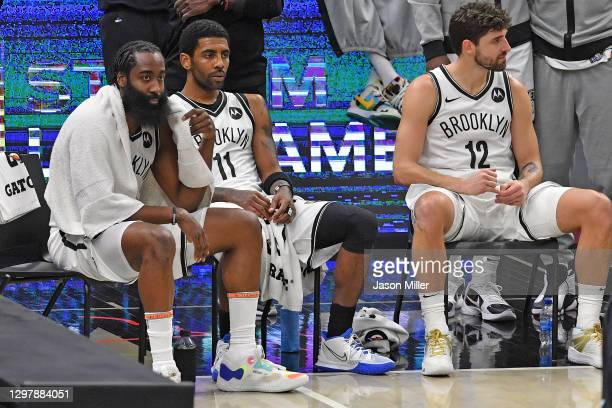 James Harden, Kyrie Irving and Joe Harris of the Brooklyn Nets sit on the bench during a timeout in the fourth quarter against the Cleveland...