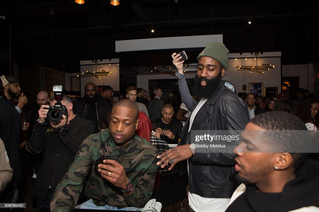 James Harden looks over Dwyane Wade's cards during a game at the Dwyane Wade and Stance Stocks Spades Tournament at The One Eighty on February 11, 2016 in Toronto, Canada.