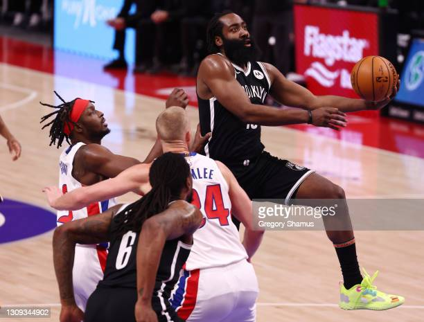 James Harden of the Brooklyn Nets drives around Mason Plumlee and Jerami Grant of the Detroit Pistons during the first half at Little Caesars Arena...