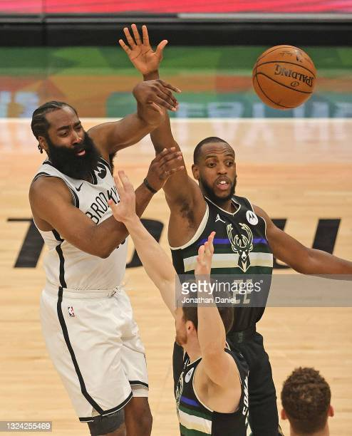 James Harden of the Brooklyn Nets passes over Khris Middleton and Pat Connaughton of the Milwaukee Bucks at Fiserv Forum on June 17, 2021 in...