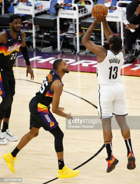 James Harden of the Brooklyn Nets puts up a three-point shot over Mikal Bridges of the Phoenix Suns during the final moments of the second half of...