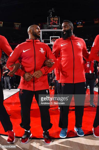 James Harden of the Houston Rockets and Chris Paul of the Houston Rockets look on during the national anthem before the game against the Portland...