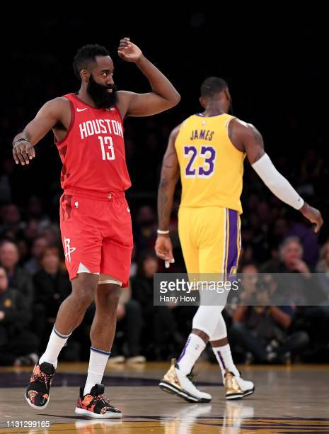 James Harden of the Houston Rockets celebrates a lead as he walks off the court after a timeout in front of LeBron James of the Los Angeles Lakers...