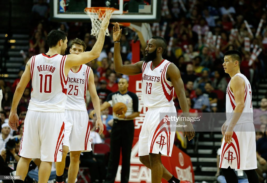 James Harden #13 of the Houston Rockets celebrates a play with Carlos Delfino #10 on the court during the game against the Brooklyn Nets at Toyota Center on January 26, 2013 in Houston, Texas.