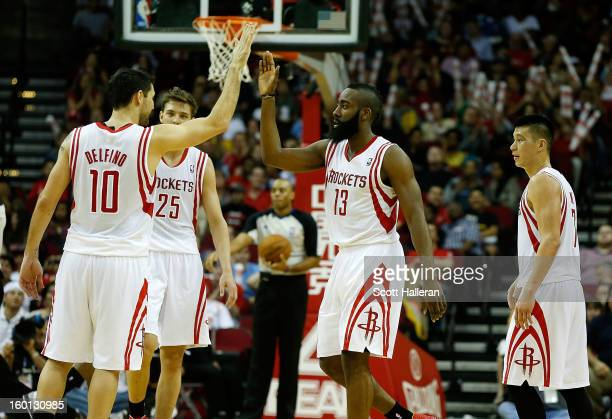 James Harden of the Houston Rockets celebrates a play with Carlos Delfino on the court during the game against the Brooklyn Nets at Toyota Center on...
