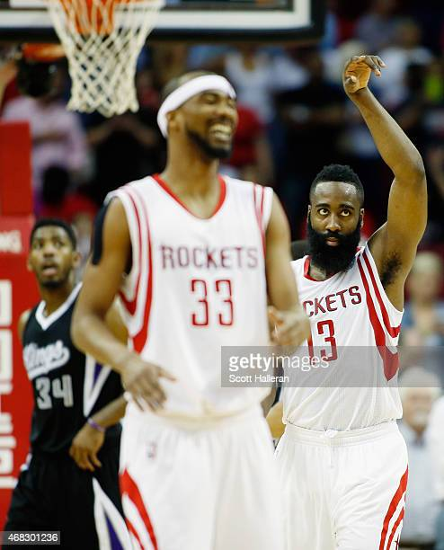 James Harden of the Houston Rockets celebrates a play with teammate Corey Brewer as Jason Thompson of the Sacramento Kings looks on during their game...