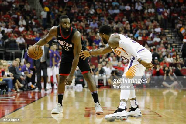 James Harden of the Houston Rockets controls the ball defended by Troy Daniels of the Phoenix Suns in the second half at Toyota Center on March 30...