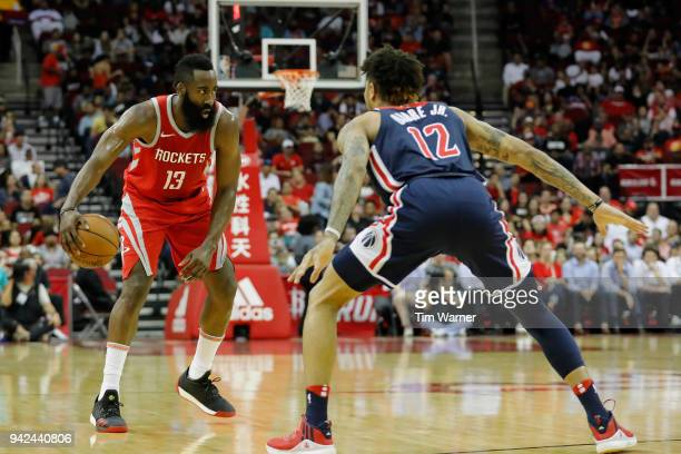 James Harden of the Houston Rockets controls the ball defended by Kelly Oubre Jr #12 of the Washington Wizards in the first half at Toyota Center on...