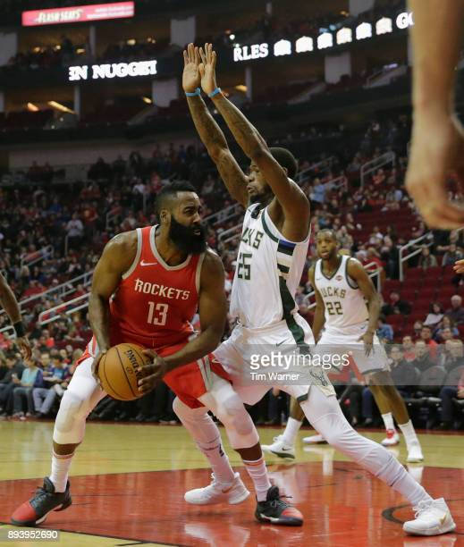 James Harden of the Houston Rockets controls the ball under the basket defended by DeAndre Liggins of the Milwaukee Bucks in the first half at Toyota...