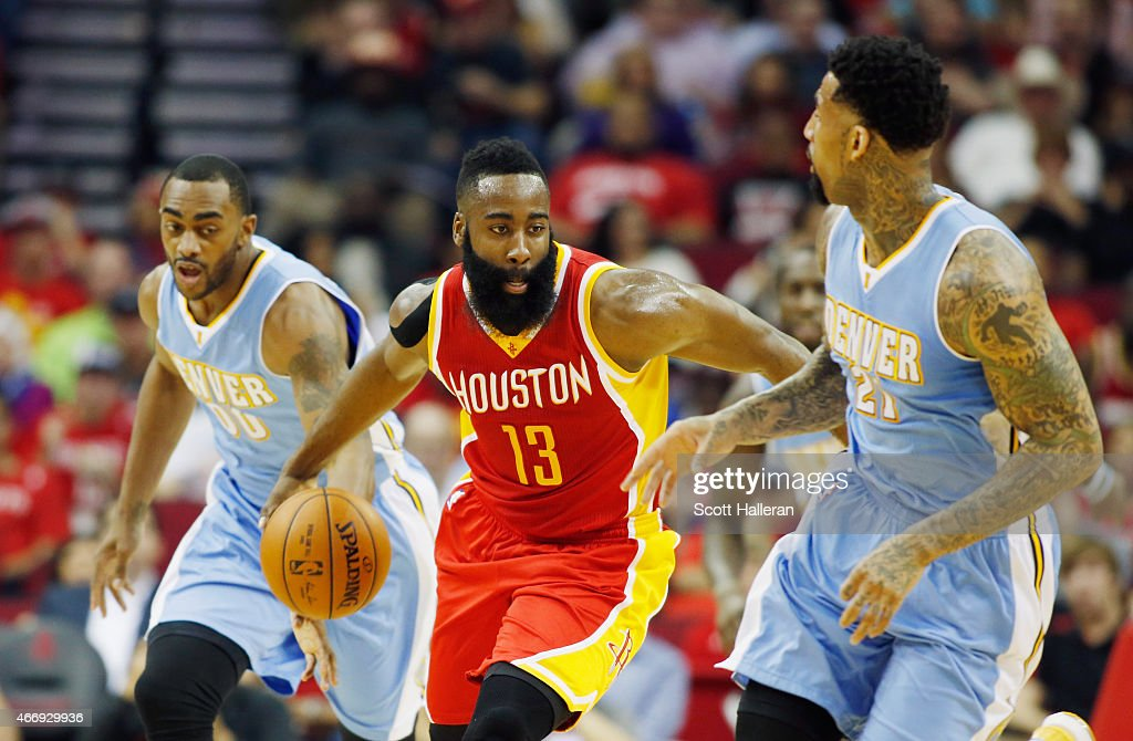 James Harden #13 of the Houston Rockets dribbles between Darrell Arthur #00 and Wilson Chandler #21 of the Denver Nuggets during their game at the Toyota Center on March 19, 2015 in Houston, Texas.