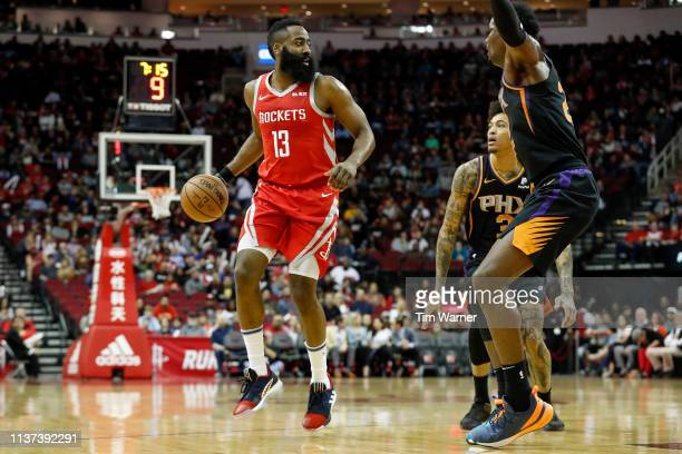 James Harden of the Houston Rockets dribbles the ball defended by Deandre Ayton of the Phoenix Suns and Kelly Oubre Jr #3 in the first half at Toyota...
