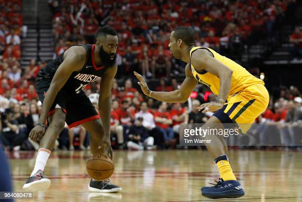 James Harden of the Houston Rockets dribbles the ball defended by Alec Burks of the Utah Jazz in the second half during Game One of the Western...