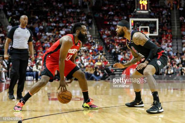 James Harden of the Houston Rockets dribbles the ball while defended by Marcus Morris Sr. #31 of the LA Clippers in the first half at Toyota Center...