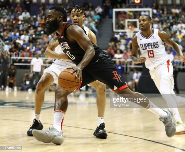 James Harden of the Houston Rockets drives around Amir Coffey of the Los Angeles Clippers during their game at the Stan Sheriff Center on October 3,...