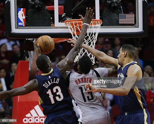 James Harden of the Houston Rockets drives between Cheick Diallo of the New Orleans Pelicans and Alexis Ajinca at Toyota Center on December 16 2016...