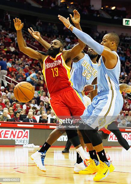 James Harden of the Houston Rockets drives between Kenneth Faried and Randy Foye of the Denver Nuggets during their game at the Toyota Center on...