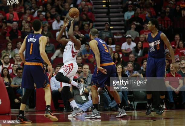 James Harden of the Houston Rockets drives past Jared Dudley of the Phoenix Suns and Devin Booker as Marquese Chriss looks on at Toyota Center on...