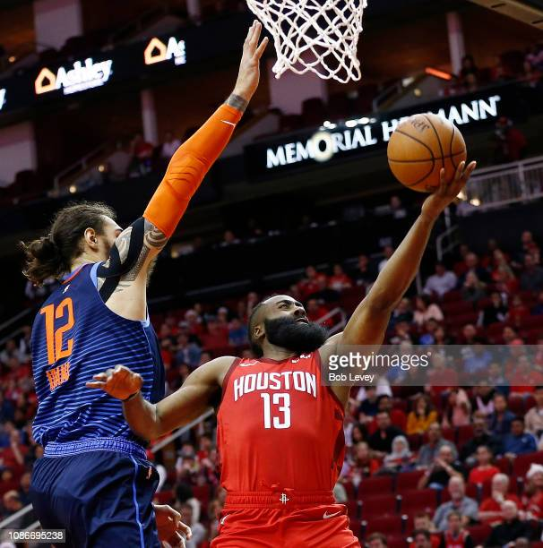 James Harden of the Houston Rockets drives past Steven Adams of the Oklahoma City Thunder for a layup during the first quarter at Toyota Center on...
