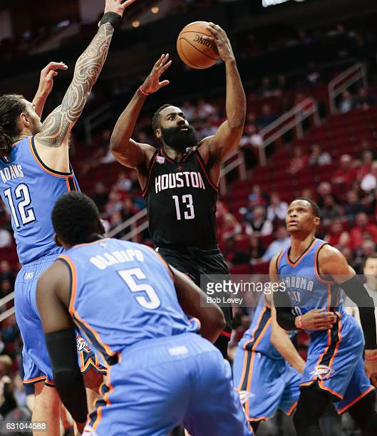 James Harden of the Houston Rockets drives to the basket between Steven Adams of the Oklahoma City Thunder Victor Oladipo and Russell Westbrook in...