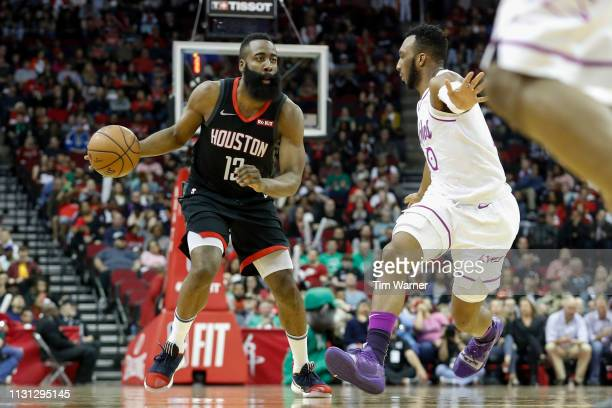James Harden of the Houston Rockets drives to the basket defended by Jeff Teague of the Minnesota Timberwolves in the first half at Toyota Center on...