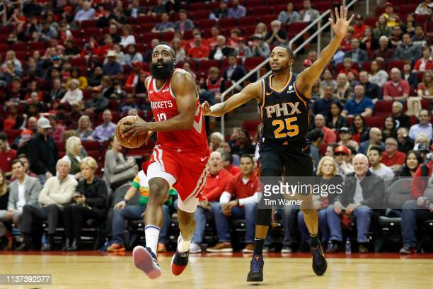 James Harden of the Houston Rockets drives to the basket defended by Mikal Bridges of the Phoenix Suns in the first half at Toyota Center on March 15...