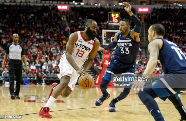 James Harden of the Houston Rockets drives to the basket defended by Robert Covington of the Minnesota Timberwolves in the first half at Toyota...