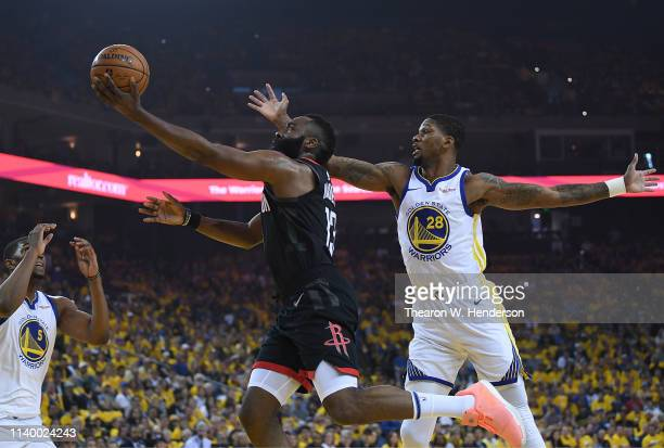 James Harden of the Houston Rockets goes in for an attempted layup over Kevon Looney and Alfonzo McKinnie of the Golden State Warriors during Game...