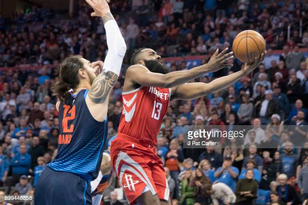 James Harden of the Houston Rockets goes past Steven Adams of the Oklahoma City Thunder for two points during the second half of a NBA game at the...