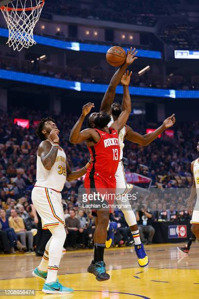 James Harden of the Houston Rockets goes to the basket against Marquese Chriss and Draymond Green of the Golden State Warriors in the first half at...