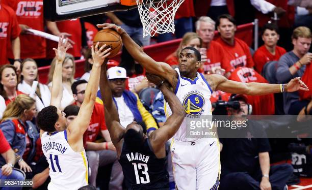 James Harden of the Houston Rockets goes up against Kevon Looney and Klay Thompson of the Golden State Warriors in the first quarter of Game Seven of...