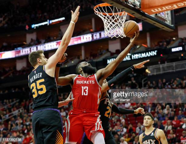 James Harden of the Houston Rockets goes up for a lay up defended by Dragan Bender of the Phoenix Suns and Richaun Holmes in the first half at Toyota...