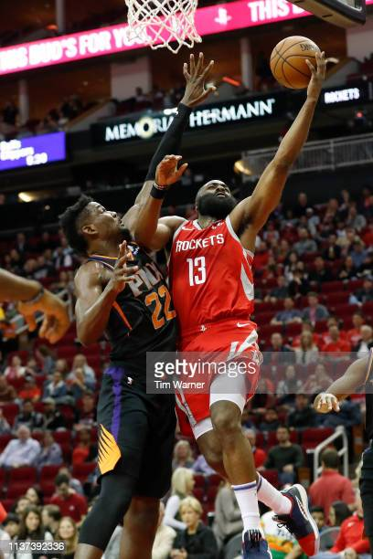 James Harden of the Houston Rockets goes up for a lay up defended by Deandre Ayton of the Phoenix Suns in the first half at Toyota Center on March 15...