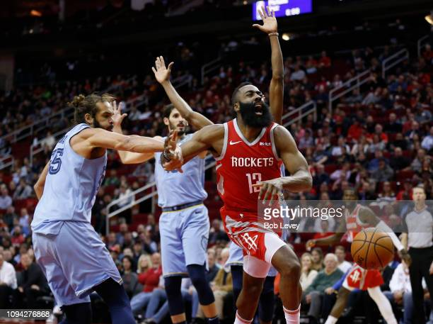 James Harden of the Houston Rockets is hit by Joakim Noah of the Memphis Grizzlies as he drives through the lane at Toyota Center on January 14 2019...