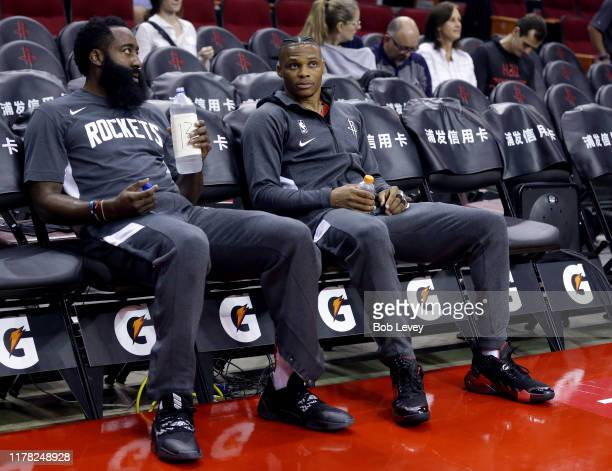James Harden of the Houston Rockets left and Russell Westbrook sit in the bench during warmups before playing a preseason game against the Shanghai...
