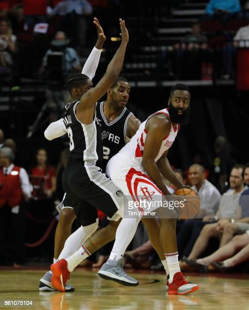 James Harden of the Houston Rockets looks to pass defended by Brandon Paul of the San Antonio Spurs and LaMarcus Aldridge in the first half at Toyota...