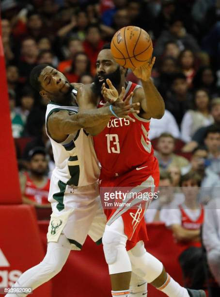 James Harden of the Houston Rockets passes the ball defended by DeAndre Liggins of the Milwaukee Bucks in the second half at Toyota Center on...